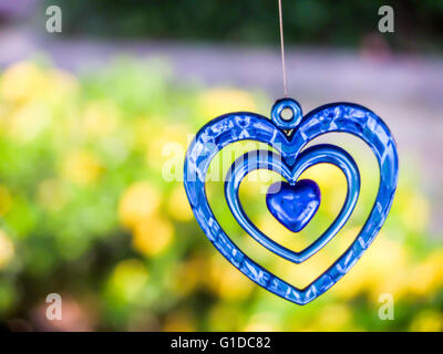 Heart a moblie decoration made of small objects tied to wires or string and hung up so that the objects move when - Stock Photo