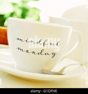 closeup of a cup of coffee or tea on a set table with the text mindful monday written in it - Stock Photo