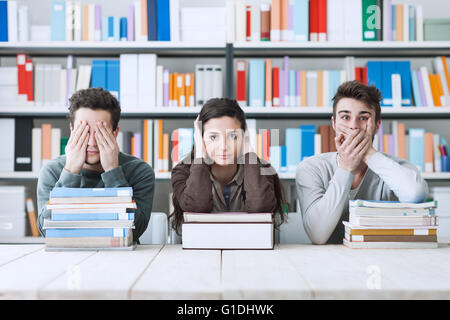 Blind, deaf and mute students covering eyes, ears and mouth, they are sitting at desk and leaning on piles of books - Stock Photo