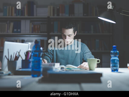 Teenage student reading books and studying late at night, learning and education concept - Stock Photo