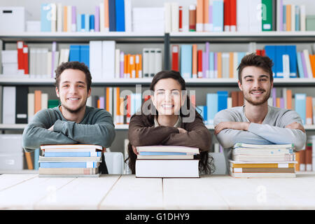 Young college students at the library studying together, they are smiling at camera and leaning on a pile of books - Stock Photo