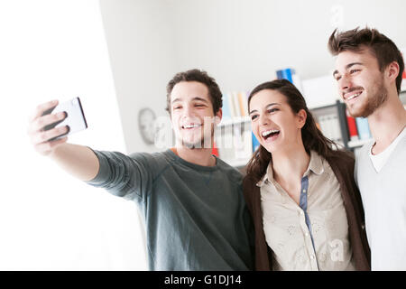Smiling happy teenagers taking selfies with a mobile phone, sharing, technology and friendship concept - Stock Photo