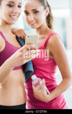 Happy young girls at the gym using a fitness app on a smart phone, technology and training concept - Stock Photo