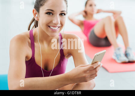 Young smiling woman at the gym having a break and listening to music using a smart phone and earphones, fitness - Stock Photo