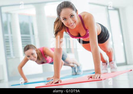 Young women at the gym doing push ups on a mat, fitness and healthy lifestyle concept