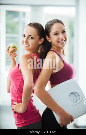 Happy teenage girl friends holding an apple and a scale, they are posing and smiling at camera, fitness and weight - Stock Photo