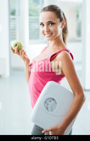 Smiling teenage girl holding a scale and a fresh apple, healthy eating, fitness and weight loss concept - Stock Photo