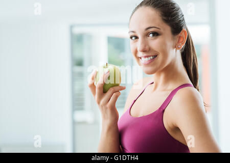 Young slim woman holding an apple and smiling at camera, healthy eating and weight loss concept - Stock Photo
