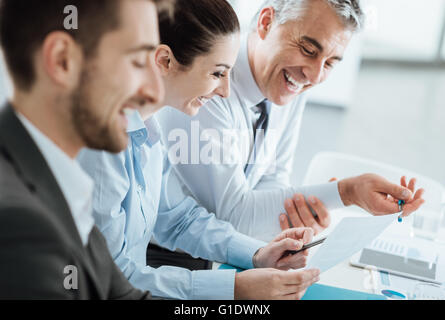Business team at work discussing on paperwork, teamwork and cooperation concept - Stock Photo