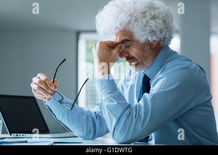 Stressed exhausted businessman sitting at office desk, failure and loss concept - Stock Photo