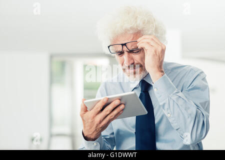 Businessman having eyesight problems, he is using a tablet and adjusting his glasses, office interior on background - Stock Photo