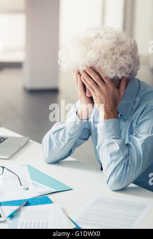 Exhausted businessman with head in hands sitting at office desk, failure and depression concept - Stock Photo