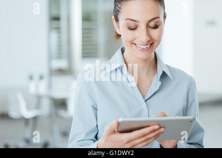 Young smiling business woman using a digital touch screen tablet and using apps, she is standing in the office - Stock Photo
