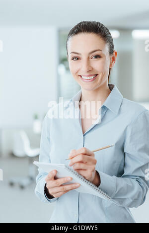 Young professional secretary writing down notes on a notebook and smiling at camera, she is standing in the office - Stock Photo
