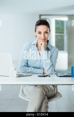 Beautiful confident female manager sitting at office desk and smiling at camera with hand on chin, room interior - Stock Photo