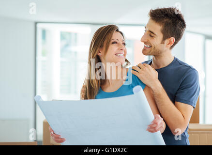 Young happy couple holding a project and planning their new house, relocation and renovation concept - Stock Photo