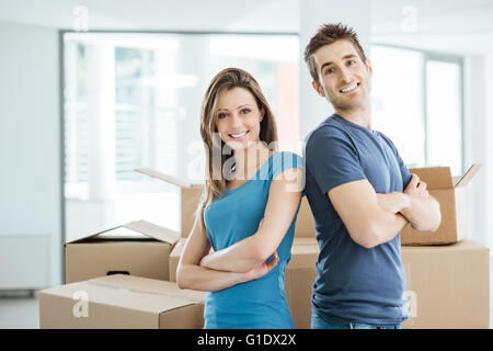 Smiling loving couple posing in their new house back to back surrounded by carton boxes - Stock Photo