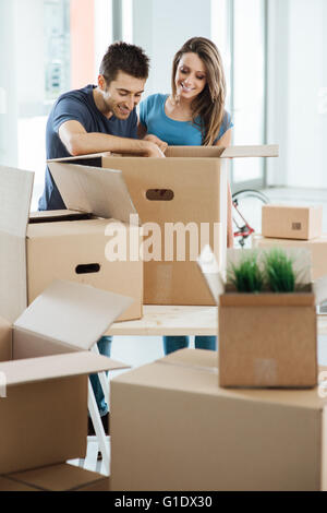 Smiling young couple unpacking carton boxes in a new house, he is searching objects in a big box on a table - Stock Photo