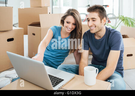 Happy couple sitting on their new house floor surrounded by carton boxes and using a wireless laptop during a coffee break