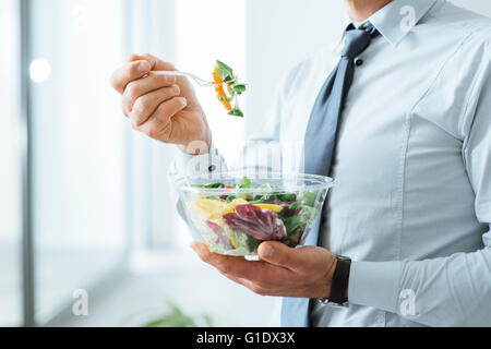 Businessman having a vegetables salad for lunch, healthy eating and lifestyle concept, unrecognizable person - Stock Photo