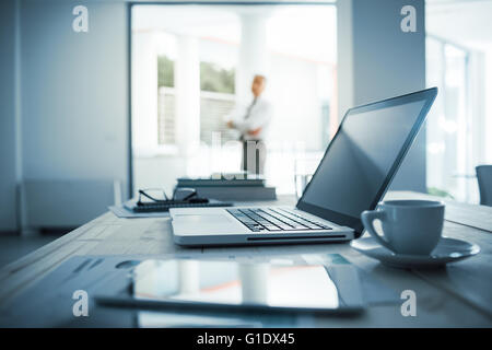 Businessman standing with arms crossed in his office, desktop with laptop on foreground, selective focus - Stock Photo
