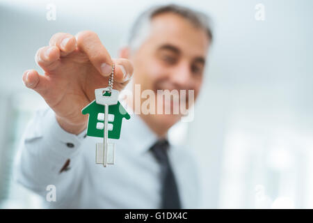 Confident real estate agent holding your new house keys and smiling at camera - Stock Photo