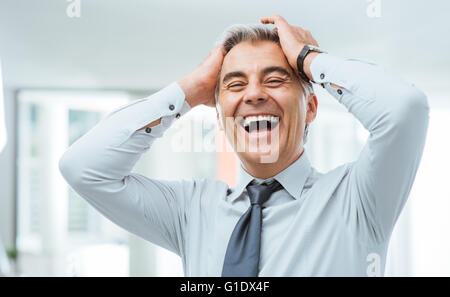 Cheerful careless businessman laughing and touching his forehead - Stock Photo