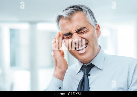 Suffering businessman having a terrible headache and touching his temples, stress and illness concept - Stock Photo