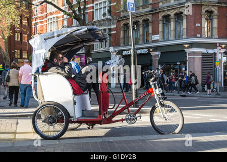 Rickshaw drivers take a rest and wait for customers outside The Palace Theatre on Cambridge Circus in  London's West End, UK