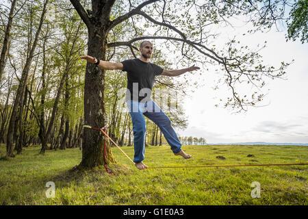 Man slacklining walking and balancing on a rope - Stock Photo