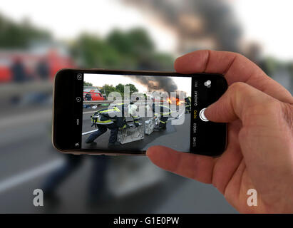 Onlookers take picture with a mobile phone camera, of an accident, symbolic image, photomontage, photo composition, - Stock Photo