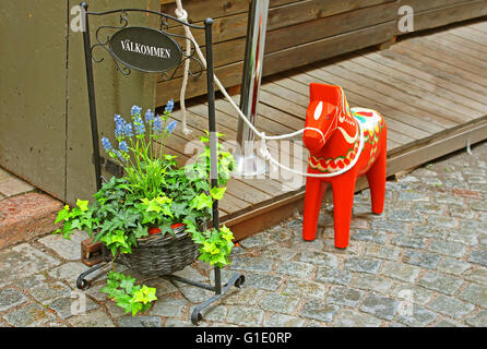 Inscription 'Welcome', flowers and a hand-made traditional wooden Dalecarlian Horse (symbol of Swedish Dalarna) - Stock Photo