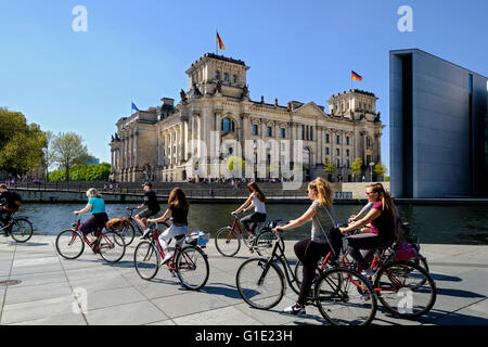 View of the Reichstag Parliament building and tourists on bicycles beside  River Spree in Berlin Germany - Stock Photo