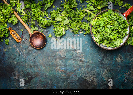 Kale in cooking pot with wooden spoon on  rustic background, top view, border. Healthy food or diet nutrition concept. - Stock Photo