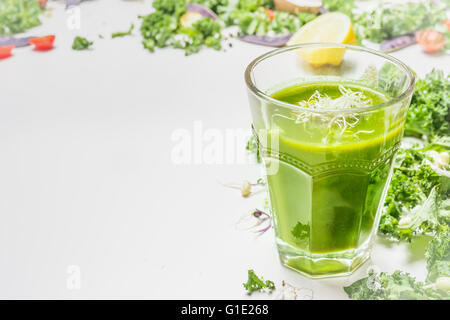 Green smoothie drink  in glass with ingredients on white wooden background, side view. Healthy food and detox  nutrition - Stock Photo