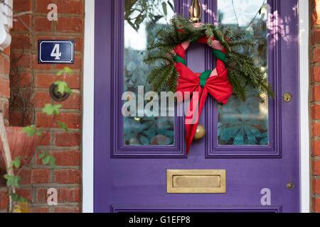 Christmas Garland on Door. Wreath hanging on purple door. - Stock Photo