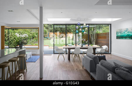 Single storey extension, Mincheon Road, London. Open plan living room and kitchen with modern furniture and glass - Stock Photo