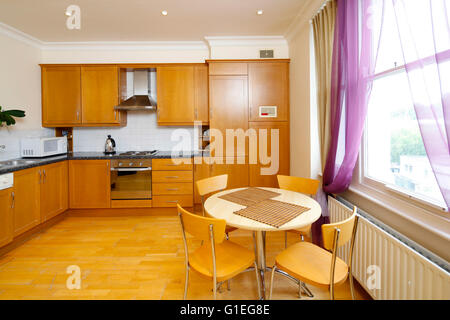 Belsize Lane, Hampstead. View of a kitchen with wood cabinets and dining table. Traditional layout. - Stock Photo