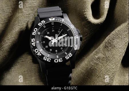 Tritium military watch on camouflage cloth - Stock Photo