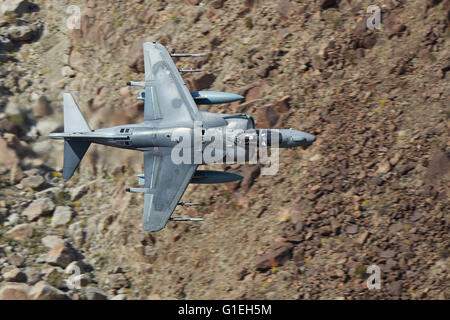 United States Marine Corps AV-8B Harrier II, Turning Hard As It Flies Low Through A Desert Canyon In The Mojave - Stock Photo