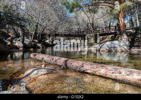 Wooden bridge over the river Manzanares along its course through La Pedriza in Guadarrama Mountains National Park, - Stock Photo