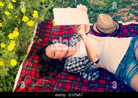 Girl reads a tablet into nature on a blanket - Stock Photo