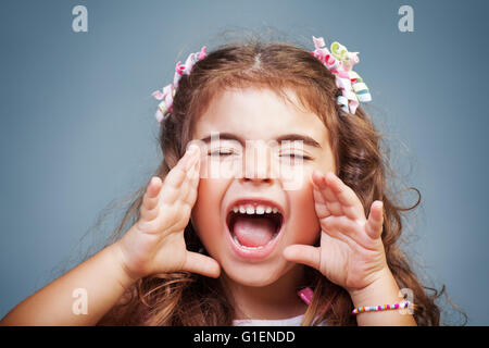 Portrait of a cute little baby girl screaming, naughty child yelling, expressing emotions, playful child rave about - Stock Photo