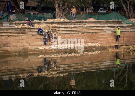Men working to restore the moat around Angkor Wat in Siem Reap, Cambodia - Stock Photo