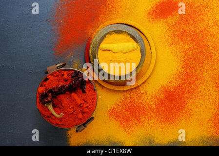 Set of spices pepper and turmeric, in vintage metal cups over yellow turmeric powder. Top view. Food or spicy cooking - Stock Photo