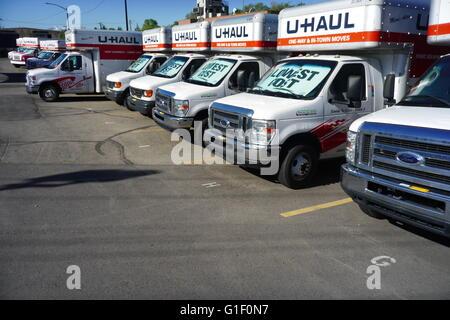U-Haul self-transportation and storage trucks on a rental lot in suburban Utah. - Stock Photo