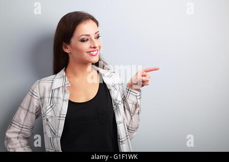 Happy casual woman showing finger on something empty on blue background - Stock Photo