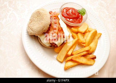 Bacon Cheeseburger Served on a Wheat English Muffin with Fried Potatoes - Stock Photo