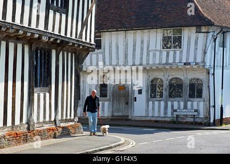 Man walking dog in the medieval village of Lavenham, Suffolk, England UK - Stock Photo