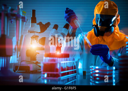 MODEL RELEASED. Person wearing protective clothing working in a microbiology laboratory. - Stock Photo